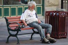 Uomo senza tetto che si siede su un banco di parco su Stephen Avenue a Calgary Alberta Immagine Stock Libera da Diritti