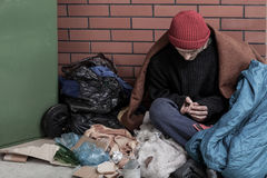 Uomo senza tetto che si siede sui rifiuti Immagini Stock Libere da Diritti