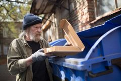 Uomo senza tetto che sta vicino alla pattumiera, tenente imballaggio dalla pizza fotografia stock libera da diritti