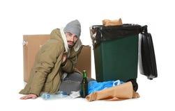 Uomo senza tetto povero che si siede vicino al bidone della spazzatura immagini stock
