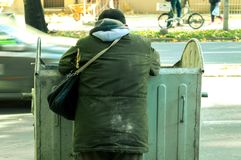 Uomo senza tetto povero ed affamato in vestiti sporchi che cercano alimento nel bidone della spazzatura sulla via urbana nella ci immagine stock