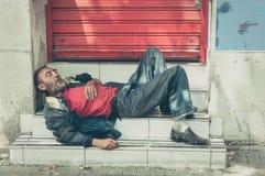 Uomo senza tetto povero o rifugiato che dorme sulle scale sulla via, concetto documentario sociale immagini stock libere da diritti