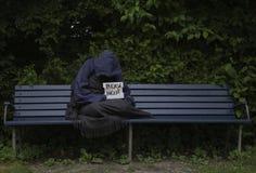 Uomo senza tetto sul banco di parco Immagini Stock Libere da Diritti