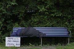 Uomo senza tetto sul banco di parco Fotografia Stock Libera da Diritti