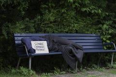 Uomo senza tetto sul banco di parco Fotografia Stock
