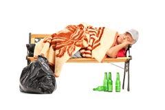 Uomo senza tetto ubriaco che dorme su un banco Immagine Stock