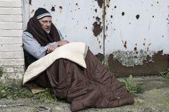 Uomo senza tetto in un vecchio sacco a pelo fotografia stock