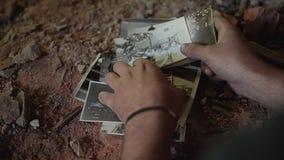 Uomo senza tetto in una costruzione rotta abbandonata che esamina le vecchie foto Ha un fronte molto triste Emozione umana video d archivio