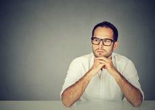 Uomo serio al pensiero della tavola fotografia stock