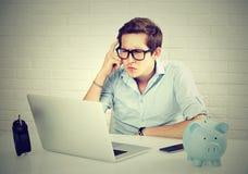 Uomo serio in camicia blu che esamina computer portatile mentre sedendosi al suo posto di lavoro Fotografie Stock Libere da Diritti
