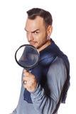 Uomo serio che guarda tramite la lente d'ingrandimento Immagine Stock