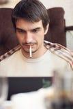 Uomo serio che lavora al computer portatile in caffè Immagini Stock Libere da Diritti