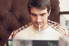Uomo serio che lavora al computer portatile in caffè Fotografie Stock