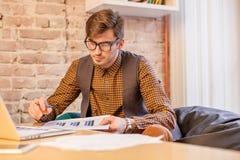 Uomo serio che lavora al computer portatile Vetri e camicia d'uso dell'uomo Immagini Stock Libere da Diritti