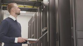 Uomo serio che lavora nella stanza del server del centro dati archivi video