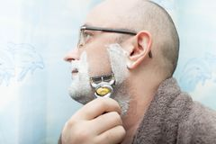 Uomo serio che rade la sua barba dalla lametta immagine stock libera da diritti