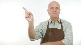 Uomo serio con il segno di attenzione del grembiule gesti di mano d'avvertimento fotografie stock