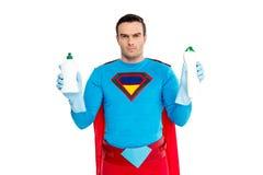 uomo serio in costume del supereroe che tiene le bottiglie con il detersivo e che esamina macchina fotografica immagine stock libera da diritti