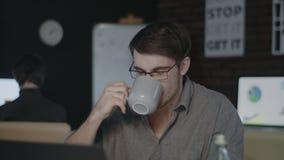 Uomo serio di affari che guarda il monitor del computer nell'ufficio di notte video d archivio