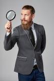 Uomo serio di affari dei pantaloni a vita bassa con la lente d'ingrandimento Fotografia Stock
