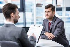 Uomo serio nell'usura convenzionale che esamina uomo d'affari con la lavagna per appunti durante l'intervista di lavoro Fotografia Stock Libera da Diritti