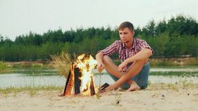 Uomo serio solo che si siede dal fuoco di accampamento, caramelle gommosa e molle dell'arrosto su un bastone stock footage