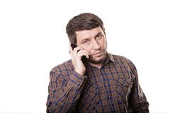 Uomo serio in una camicia di plaid che parla sul telefono isolato su wh immagini stock