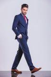 Uomo serio in vestito che cammina con le mani in tasche Fotografia Stock Libera da Diritti
