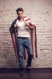 Uomo sexy che per mezzo della bandiera americana come un mantello. Fotografie Stock