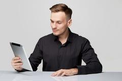 Uomo sicuro alla tavola su fondo isolato con la tavola ed il telefono Fotografia Stock Libera da Diritti