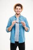 Uomo sicuro allegro in cappello ed occhiali da sole blu della tenuta della camicia Fotografie Stock