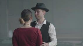 Uomo sicuro bello del ritratto in uno scherzo di sussurro del cappello sull'orecchio di signora elegante che condizione con lei d stock footage