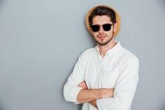 Uomo sicuro in cappello ed occhiali da sole che stanno con le armi attraversate Fotografia Stock Libera da Diritti