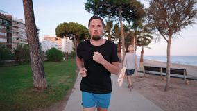 Uomo sicuro che corre sulla spiaggia stock footage
