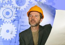 Uomo sicuro dell'ingegnere industriale nel casco del costruttore che controlla i modelli della costruzione di edifici su sviluppo immagine stock