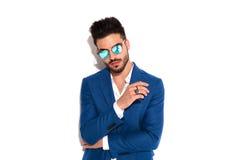 Uomo sicuro di modo in occhiali da sole e cappotto blu Immagini Stock Libere da Diritti