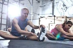 Uomo sicuro e donna che fanno allungando esercizio nella palestra del crossfit Immagine Stock