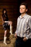 Uomo sicuro e giovane donna nella capanna di legno del libro macchina Fotografie Stock