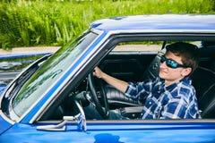 Uomo sicuro fresco in occhiali da sole che conducono automobile Fotografia Stock