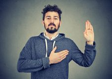 Uomo sincero che giura con la mano su cuore Immagini Stock