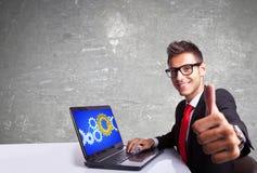 Uomo soddisfatto di affari che lavora al computer portatile e che fa segno giusto Fotografie Stock Libere da Diritti
