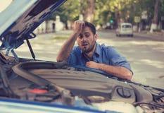 Uomo sollecitato che ha difficoltà con l'automobile rotta che esamina nella frustrazione il motore guastato fotografia stock libera da diritti