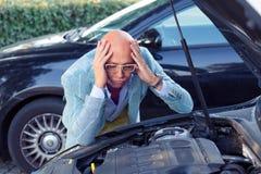 Uomo sollecitato che ha difficoltà con l'automobile rotta fotografie stock libere da diritti