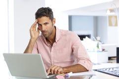 Uomo sollecitato che lavora al computer portatile in Ministero degli Interni Fotografia Stock