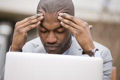 Uomo sollecitato che si siede fuori dell'ufficio corporativo che lavora al computer Immagine Stock Libera da Diritti