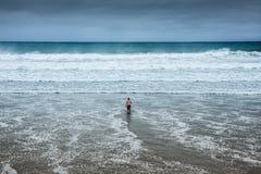 Uomo solo che entra nell'acqua alla spiaggia nuvolosa Fotografie Stock Libere da Diritti