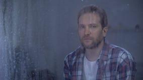 Uomo solo che esamina macchina fotografica attraverso la finestra il giorno piovoso, problemi di depressione video d archivio