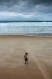 Uomo solo che fissa alla spiaggia nuvolosa Immagine Stock