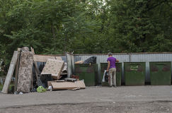 Uomo solo che rovista in un bidone della spazzatura Fotografia Stock