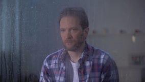 Uomo solo che si siede dietro la finestra piovosa e che esamina macchina fotografica, depressione stock footage